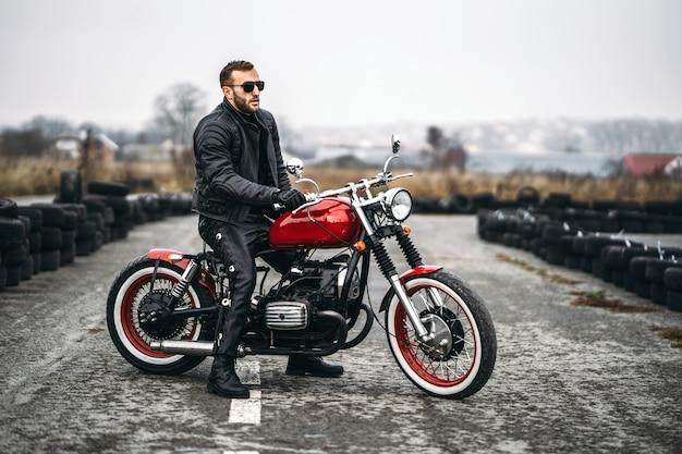 Rotes motorrad mit mitfahrer. mann in schwarzer lederjacke und hose steht seitlich mitten auf der straße.