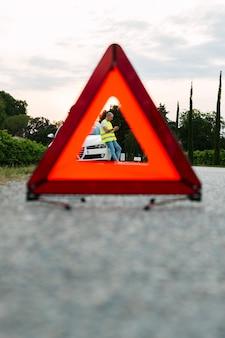 Rotes notauszeichen und junger mann, welche die autounterstützung mit defektem auto auf der straße warten