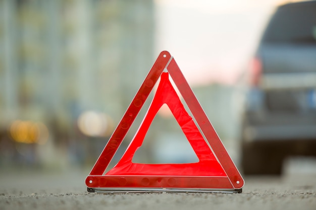 Rotes notdreieckstoppschild und defektes auto auf einer stadtstraße.