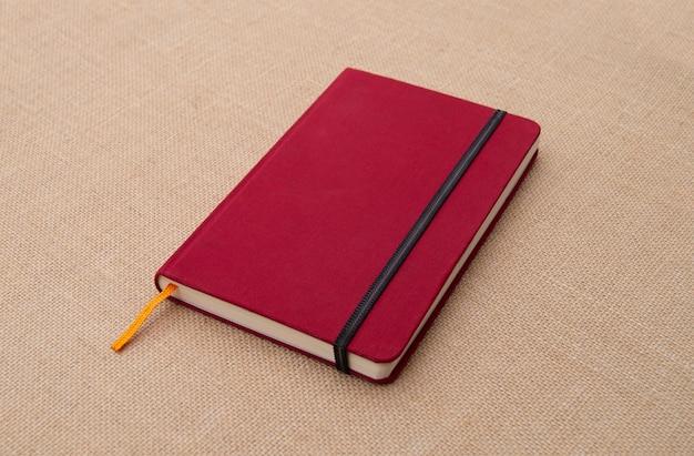 Rotes notizbuch auf stoffoberfläche