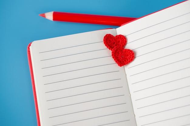 Rotes notizbuch mit bleistift und zwei gestrickten herzen auf einem blauen hintergrund. grußkarte zum valentinstag.