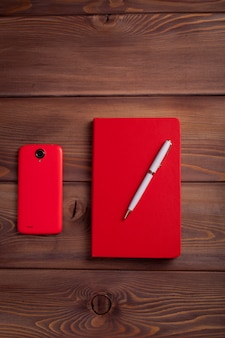 Rotes notizbuch und ein smartphone.
