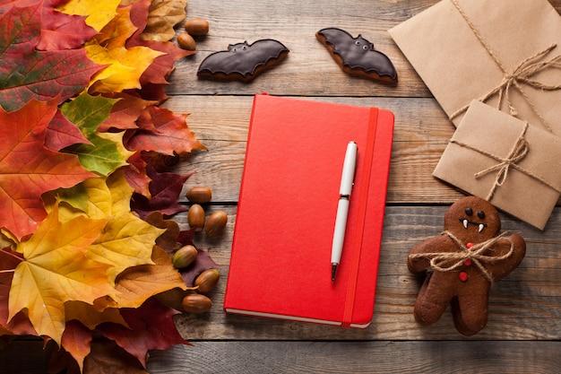 Rotes notizbuch und plätzchen für halloween.