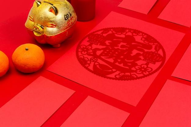 Rotes paket des chinesischen neuen jahres und goldschweinbank auf einer asiatischen kultur des roten hintergrunds. textraumbilder.