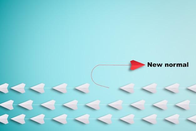 Rotes papier flugzeug außerhalb der linie mit weißem papier, um störungen zu ändern und neuen normalen weg auf blauem hintergrund zu finden.