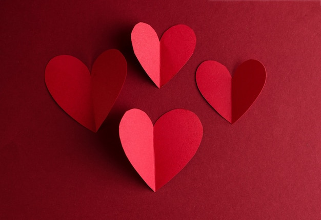 Rotes papier herzen auf einem dunklen rot. monochrome konzeptkarte zum valentinstag
