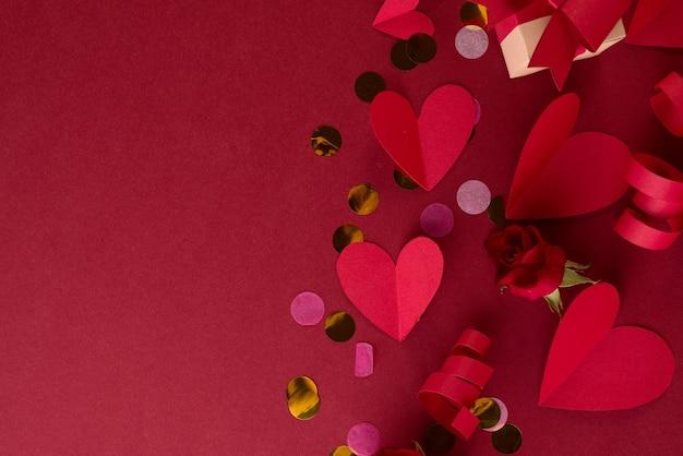 Rotes papier herzen, festliches dekor und konfetti auf einem dunklen rot.