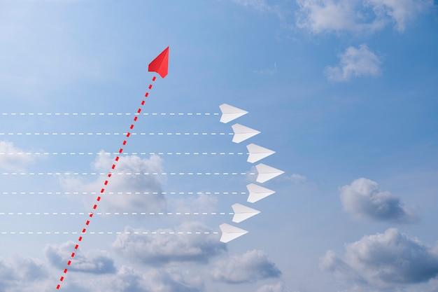 Rotes papierflugzeug außerhalb der linie mit weißem papier, um störungen zu ändern und neuen normalen weg auf himmelhintergrund zu finden. lift und geschäftskreativität neue idee zur entdeckung von innovationstechnologie.