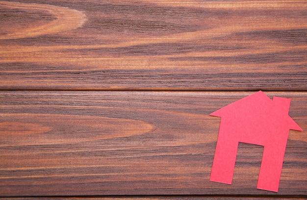 Rotes papierhaus auf einem braunen hölzernen hintergrund