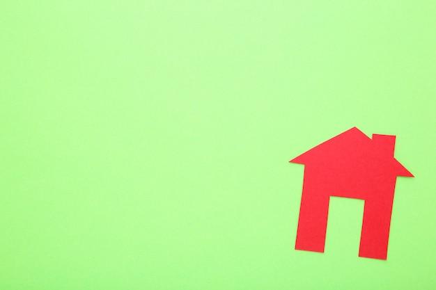 Rotes papierhaus auf einem kalkhintergrund