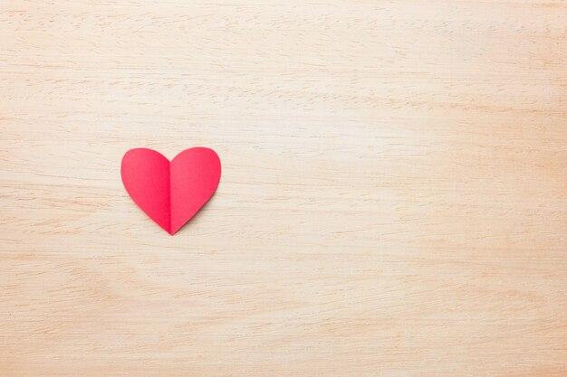 Rotes papierherz auf hölzernem hintergrund, liebe und valentinsgrußkonzept