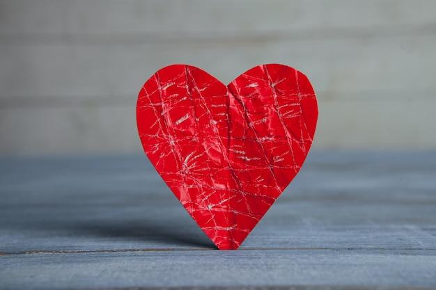 Rotes papierherz auf holzoberfläche
