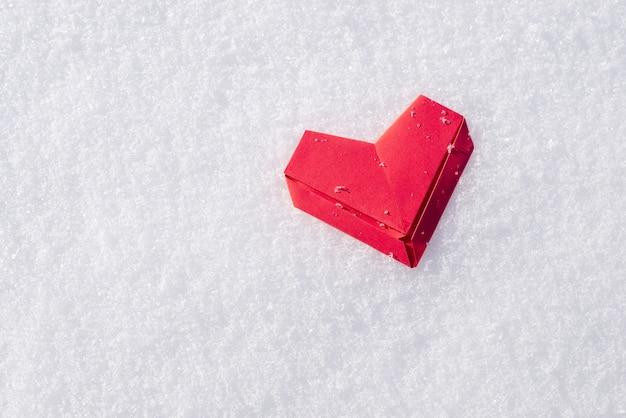 Rotes papierherz auf weißem schnee mit kopienraum