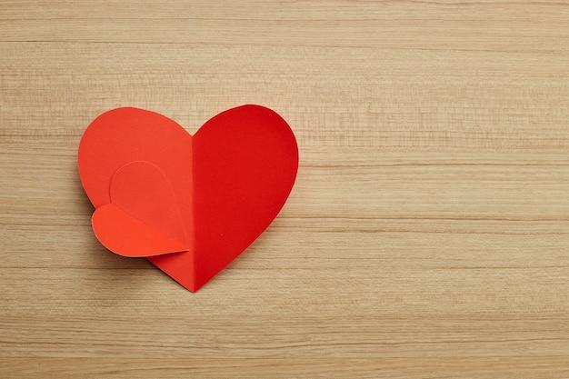 Rotes papierherz des valentinstags auf hölzernem
