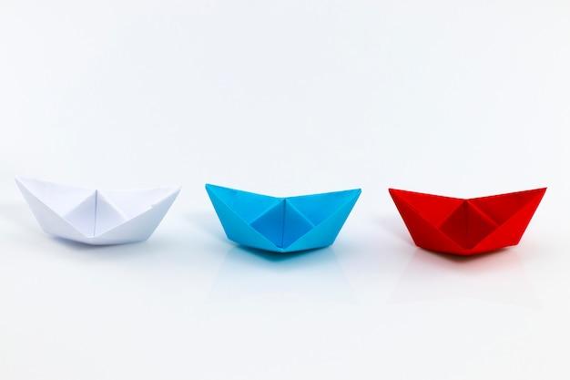 Rotes papierschiff, blaues papierschiff und weißes papierschiff