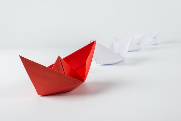 Rotes papierschiff, das unter weiß führt