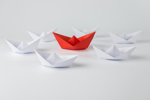 Rotes papierschiff, das unter weißem hintergrund führt