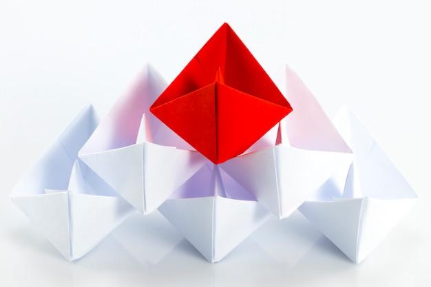Rotes papierschiff, das unter weißen papierschiffen führt