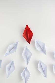 Rotes papierschiff, das weiße führt