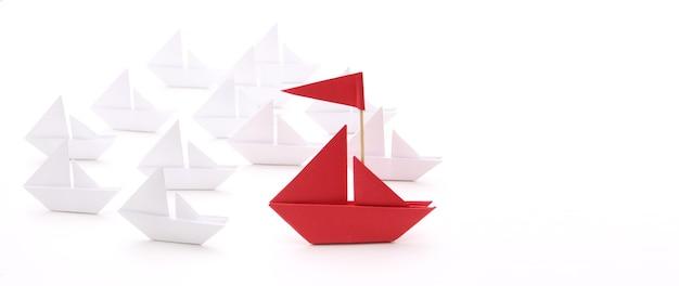 Rotes papierschiff mit kleinen booten. führungskonzept.