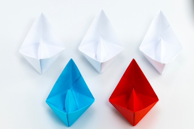 Rotes papierschiff und blaues papierschiff führen unter weißen papierschiffen
