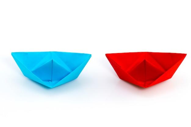Rotes papierschiff und blaues papierschiff
