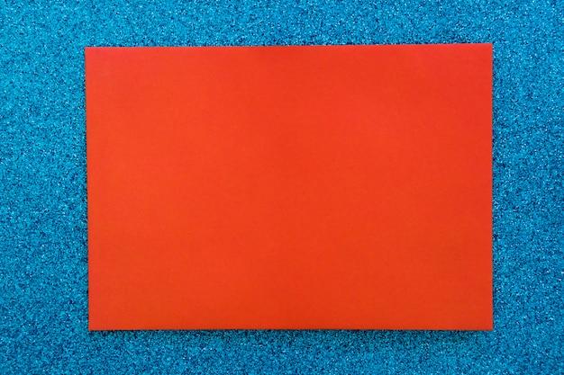 Rotes papppapier auf blauem funkelnhintergrund