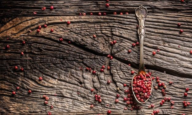 Rotes pfefferkorn auf löffel auf eichentisch.