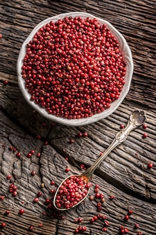Rotes pfefferkorn in schüssel und löffel auf eichentisch.