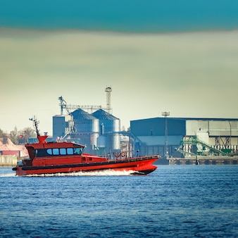 Rotes pilotschiff, das an der fabrik in lettland vorbeifährt
