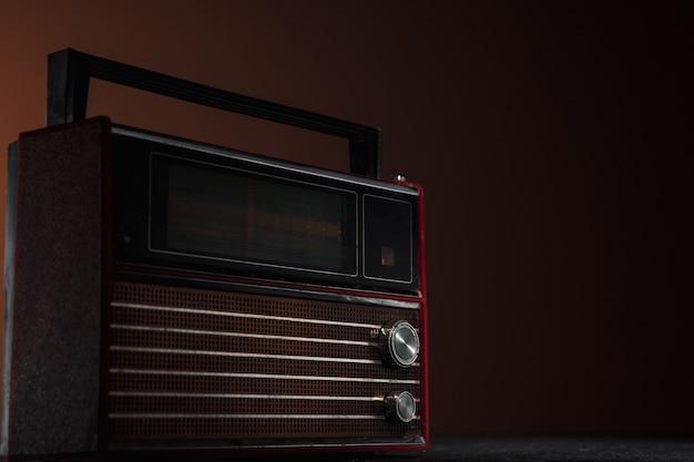 Rotes radio auf dunklem hintergrund. nahaufnahme von alten retro-dingen, die mit farben im vintage-stil geschossen und getönt wurden.