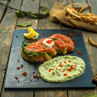 Rotes räucherfischsandwich der seitenansicht mit sauerrahmmais und soße auf tablett