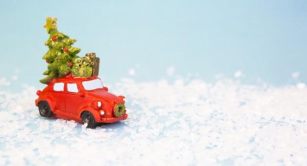 Rotes retro-auto auf kunstschnee trägt einen weihnachtsbaum mit geschenkboxen auf dem dach
