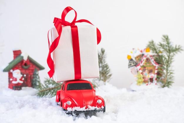 Rotes retro-spielzeugauto, das weihnachts- oder neujahrsgeschenke auf dem dach gegen schneeweißen hintergrund liefert