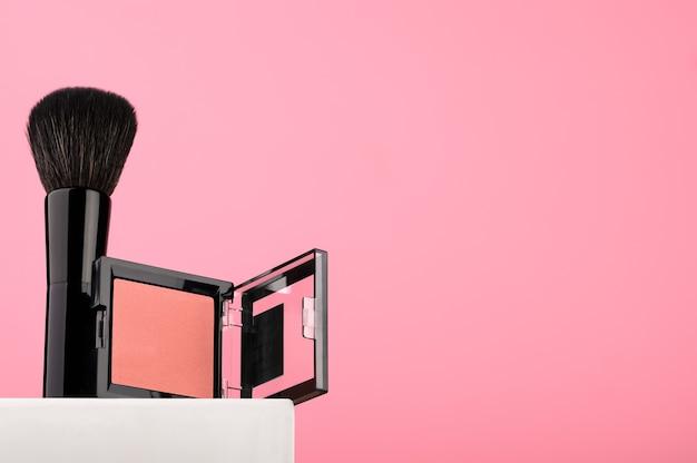 Rotes rouge mit schwarzem pinsel auf weißem ständer, vitrine für kosmetik. damen-beauty-accessoire für professionelles make-up. ein produkt für den perfekten hautton. platz kopieren.