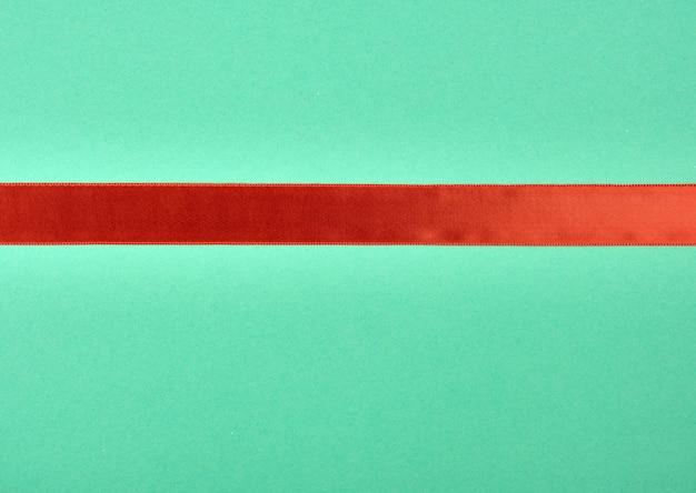 Rotes satinband auf grünem hintergrund
