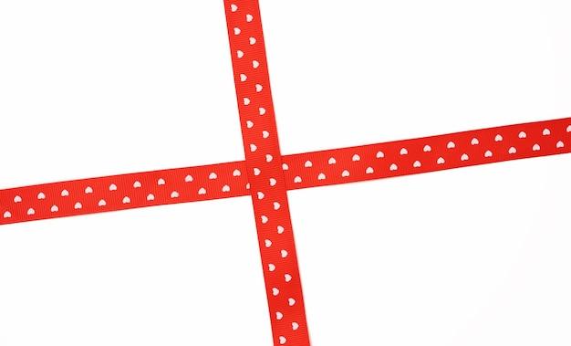 Rotes satinband kreuz zum kreuzen auf weißem hintergrund, geschenkverpackung