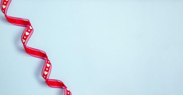 Rotes satinband mit herzen auf blauem hintergrund - valentinstagfahne