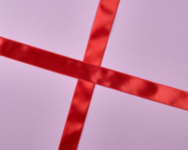 Rotes satinbandkreuz, zum auf purpurrotem hintergrund zu kreuzen
