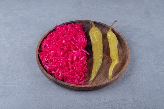Rotes sauerkraut und peperoni an bord, auf dem marmorhintergrund.