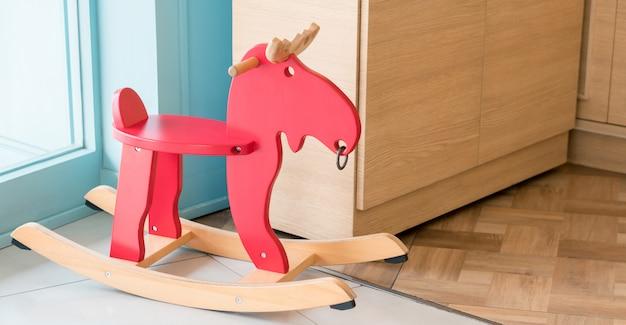 Rotes schaukelpferdspielzeug für kind im hauptwohnzimmer