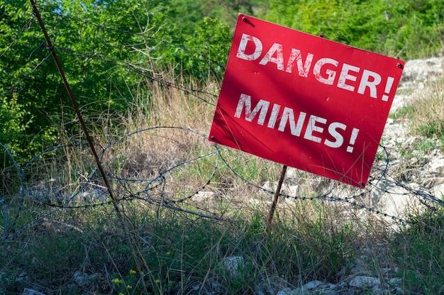Rotes schild gefahr minen vor einem mit stacheldraht eingezäunten minenfeld