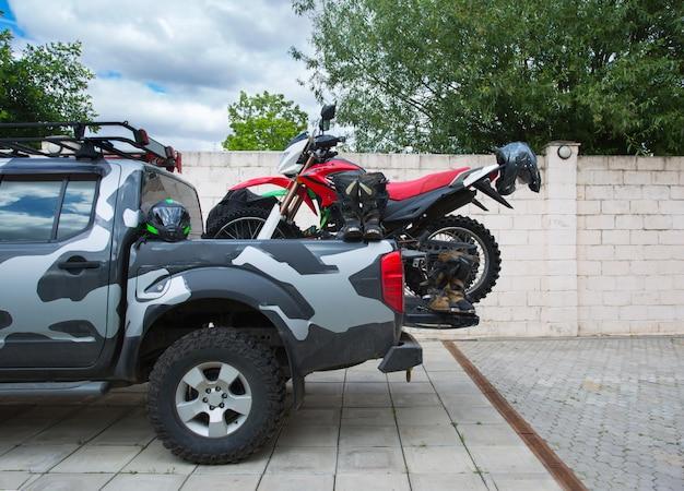 Rotes schmutzfahrradmotorrad auf der rückseite des camouflage-lkws mit sicherheitsausrüstung.