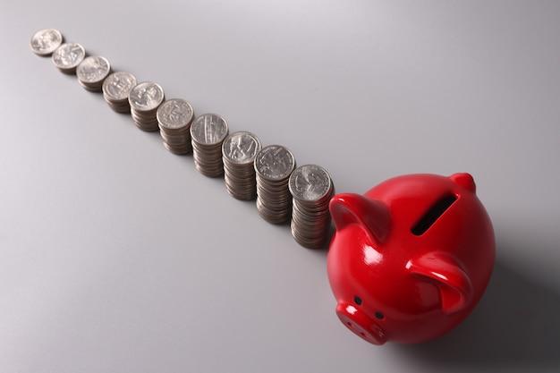 Rotes schwein sparschwein und stapel von münzen draufsicht