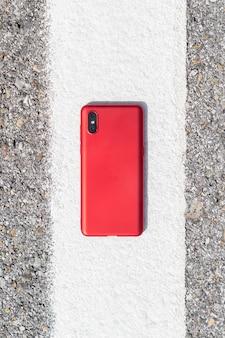 Rotes smartphone auf weißer linie über straße