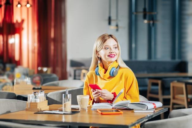 Rotes smartphone. junge blonde freiberuflerin, die ihr rotes smartphone am tisch hält