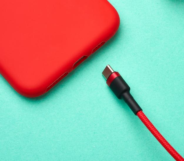 Rotes smartphone und kabel im textilgeflecht auf grünem hintergrund