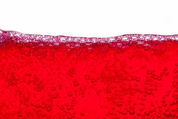 Rotes sodawasser, das mit den blasen nah oben und taupunkt auf glas spritzt