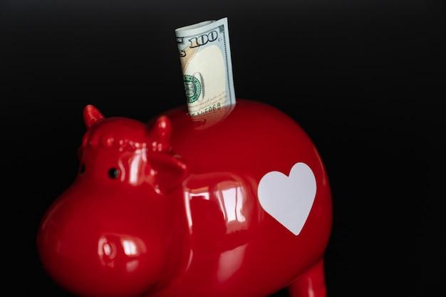 Rotes sparschwein in form einer kuh mit 100 dollar auf schwarzem hintergrund. geld anlegen und aufbewahren. das konzept der sparsamkeit und der finanziellen bildung.