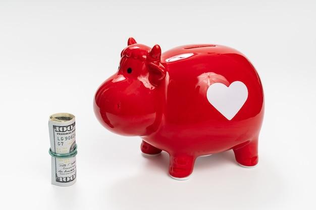 Rotes sparschwein in form einer kuh mit 100 dollar auf weißem hintergrund. geld anlegen und aufbewahren. das konzept der sparsamkeit und der finanziellen bildung.